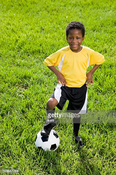 Young African American boy standing with soccer ball