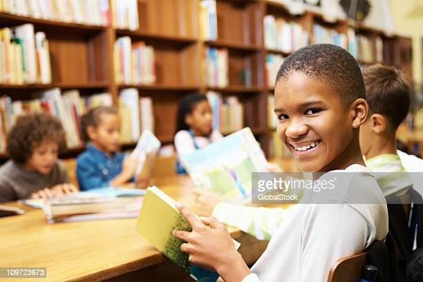 Young African American boy studying in school library