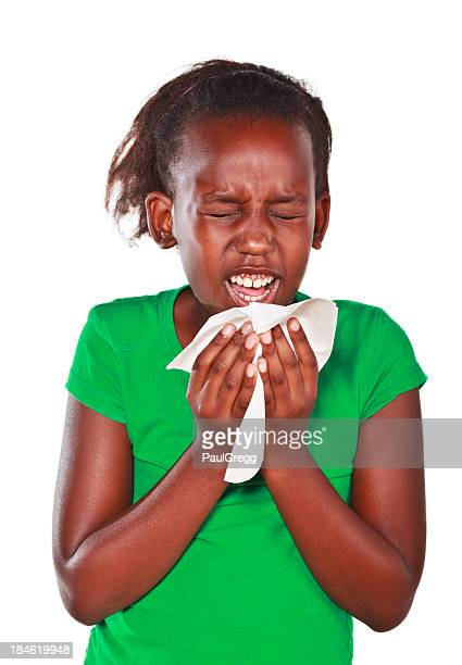 Young African American child sneezing.
