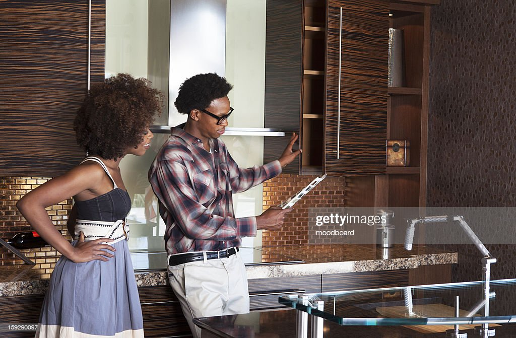 Young African American couple in new furnished Kitchen choosing materials : Stock Photo