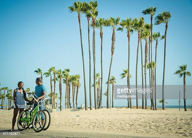 Young African American couple on bikes at Venice beach