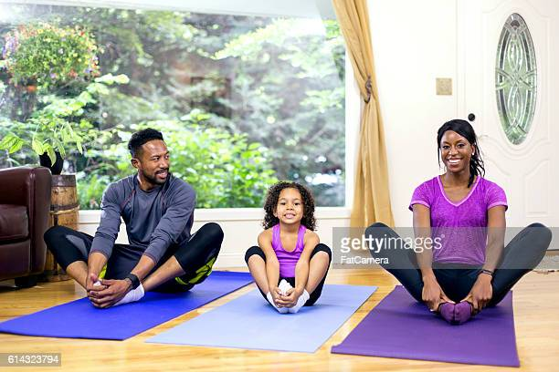 Young African American family doing yoga together in a studio