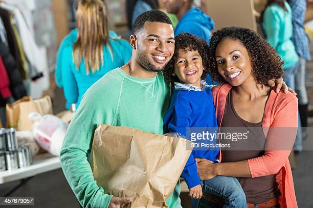Young African American family donating groceries together at food bank