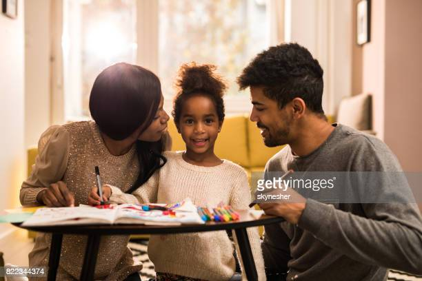 Young African American family drawing at home and enjoying in creative time together.