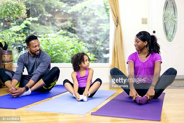 Young African American family stretching together on mats