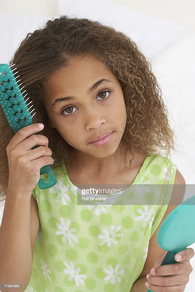 Young African American girl brushing hair