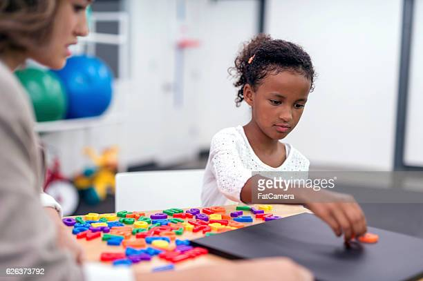 Young African American girl doing a puzzle for therapy