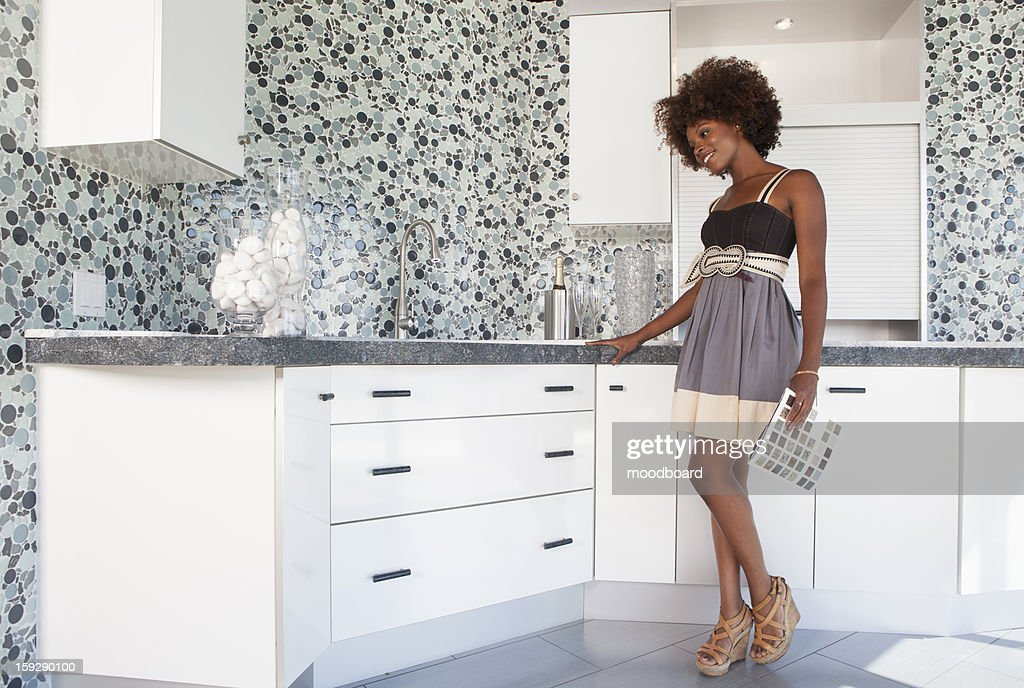 Young African American girl in new furnished Kitchen choosing materials : Stock Photo