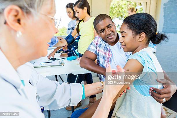 Young African American Girl in pain receiving a vaccination