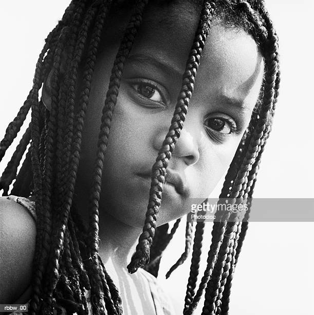 A young african american girl peers through her braids with a look of attitude