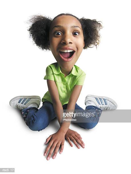young african american girl sits on floor with hands crossed in front looks at camera with surprise