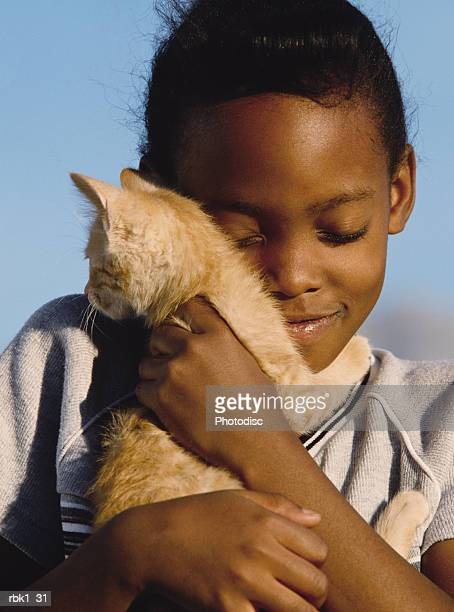A young african american girl snuggles with a kitty and a smile