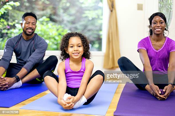 Young African American girl stretching with her family