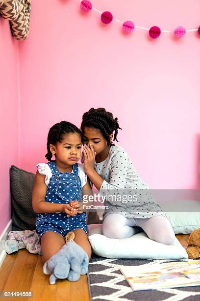 Young African American girl whispering a secret to her sister