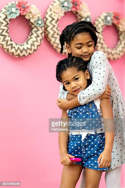 Young African American girls hugging each other