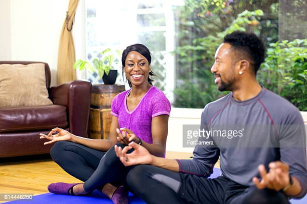Young African American heterosexual couple meditating after exercising