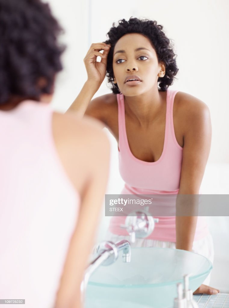 Young African American looking at her face in the mirror : Stock Photo