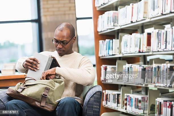Jovem homem afro-americanos na biblioteca