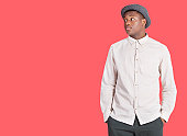 Young African American man looking sideways over red background