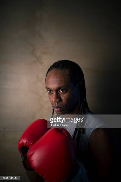 A young African American man poses in boxing gloves.