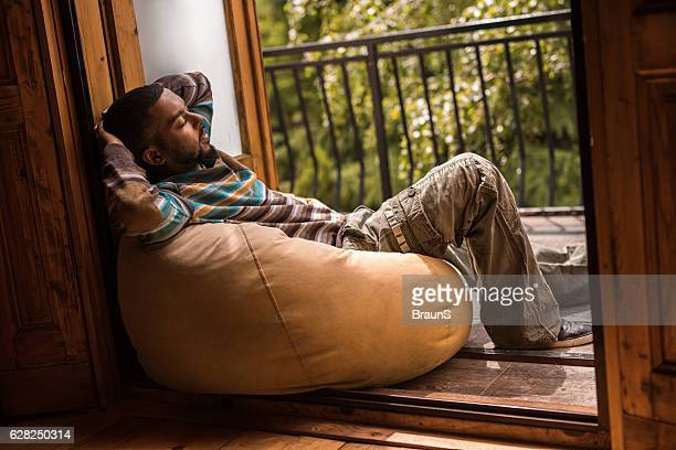 Young African American man relaxing on a bean bag.