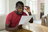 Young african american man sitting on couch in modern apartment with mouth open, holding utility bill with high rates, raised eyeglasses in wow or surprise gesture
