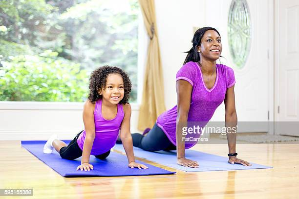 Young African American mother and daughter doing downward dog