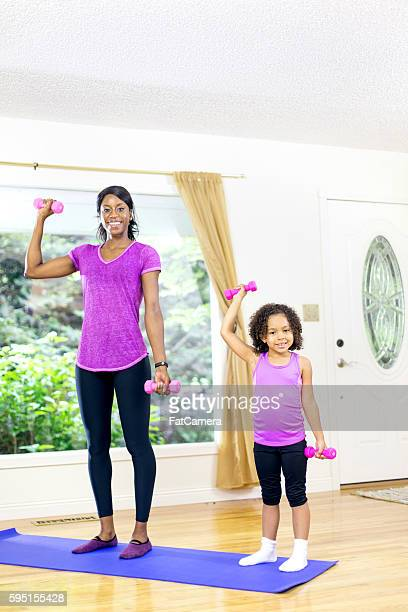 Young African American mother and daughter lifting weights