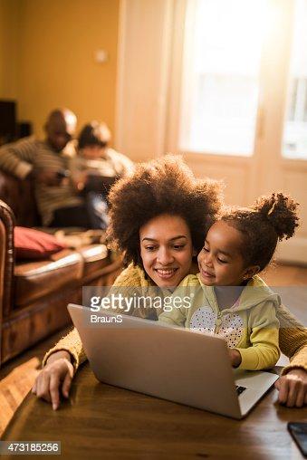 Giovane madre afro-americana e figlia usando il portatile a casa.