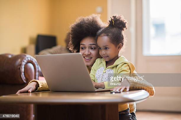 Young African American mother and her little girl using computer.