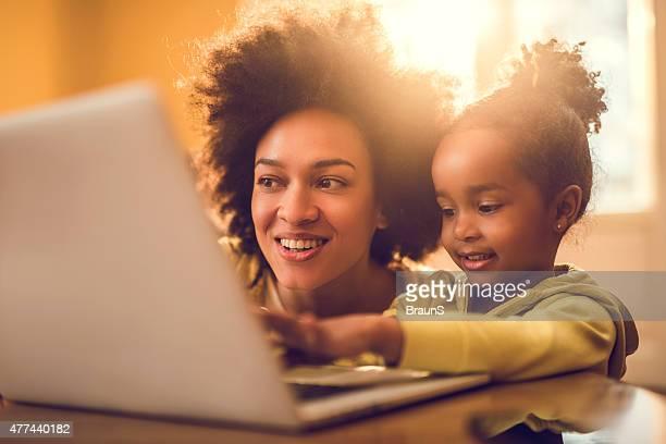 Jeune mère afro-américaine et sa petite fille à l'aide d'un ordinateur.