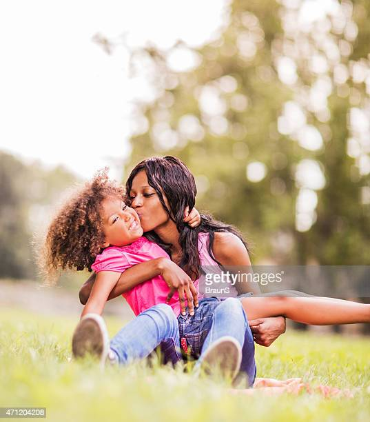 Young African American mother kissing her little daughter outdoors.