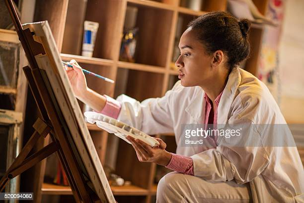 Young African American painter working in her studio.