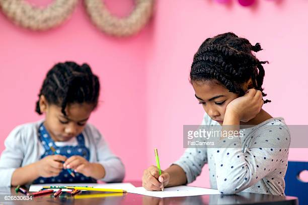 Young African American sisters drawing with colored pencils at table