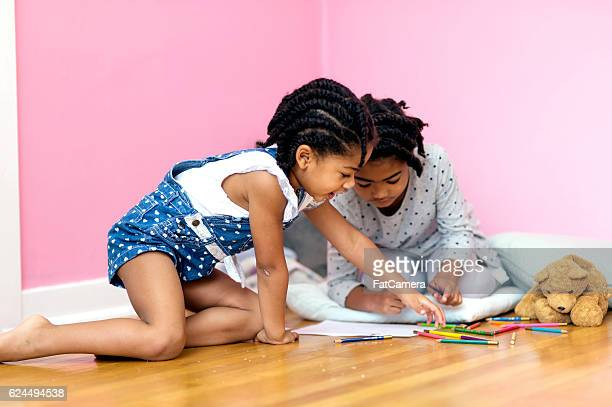 Young African American sisters playing on a wooden floor