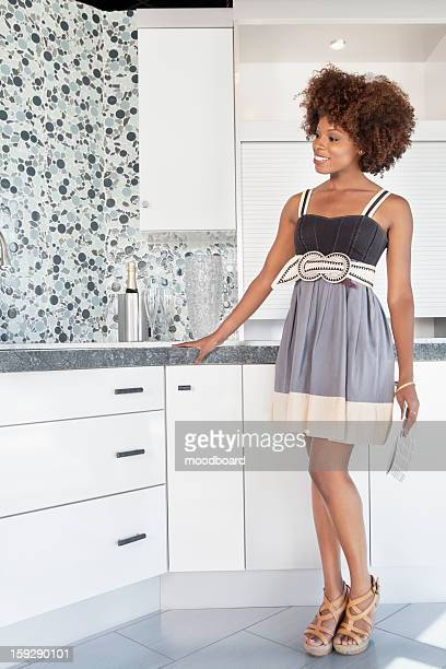 Young African American woman admiring designed wall in new house kitchen