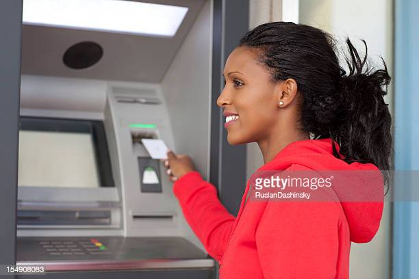 Young African American woman at an ATM wearing a red hoodie