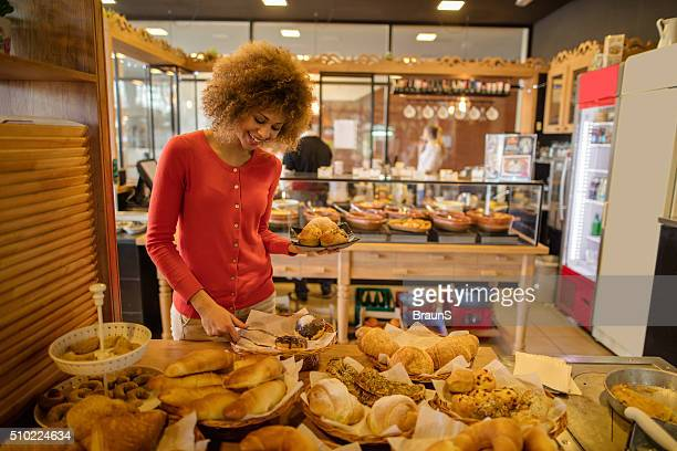 Young African American woman choosing pastry in a cafeteria.