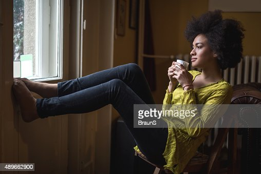 Young African American woman enjoying in coffee time at home.