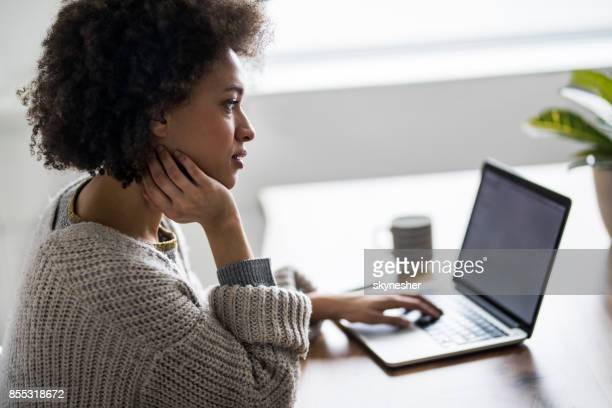 Young African American woman reading an e-mail on laptop.