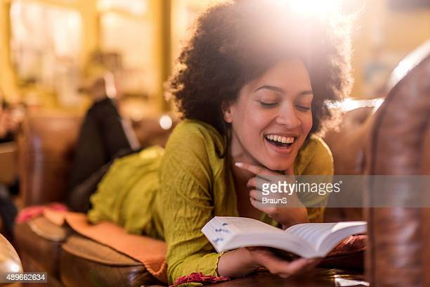 Young African American woman reading un interesante libro en su hogar.