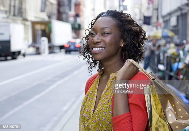 Young African American woman shopping in downtown city