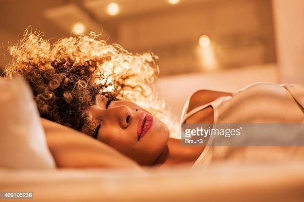Young African American woman sleeping in bed.