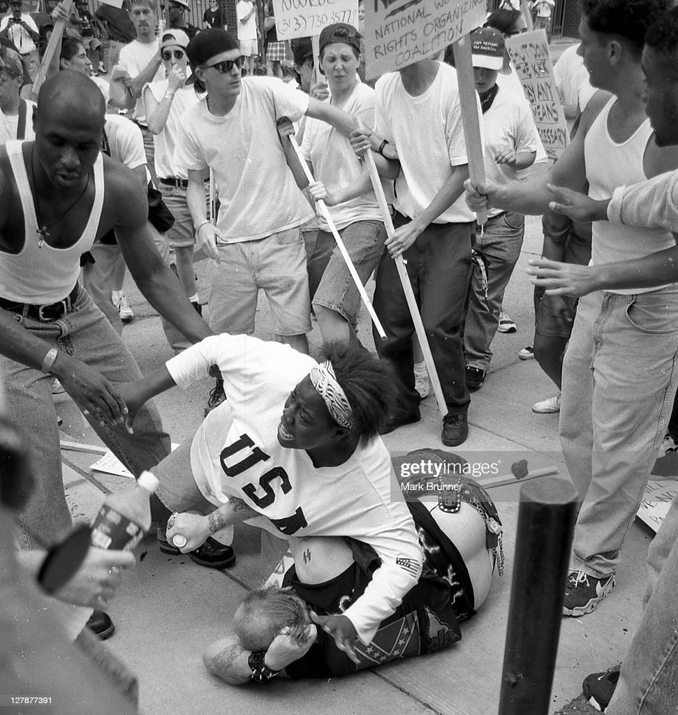 A young African American woman steps in to protect a nazi.June 22, 1996. A dozen members of a self-anointed and unwelcome KKK group came to Ann Arbor to hold a thumb-in-your-eye rally at City Hall. A protest group, the National Women's Rights Organizations Coalition (NWROC) formed to oppose them. After the rage had been mounting for awhile, this simpleminded redneck wandered up, wearing a Confederate-flag T-shirt. The crowd tore off after him, he fell, and the mob pounced. Keshia Thomas, horrified, threw herself over him to stave off the angry blows. Moments earlier, Thomas, 18, had been in the NWROC group, shouting at the KKK. It was a heroic and passionate moment in a crazy afternoon, well captured in these photographs.