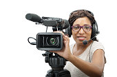 a young African American women with professional video camera and headphone on white