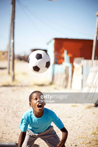 Young African boy heading a soccer ball, Cape Town, South Africa