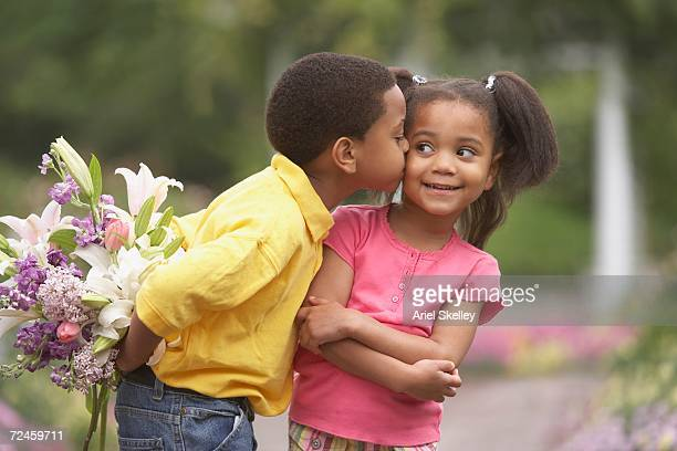 Young African boy kissing young African girl on cheek