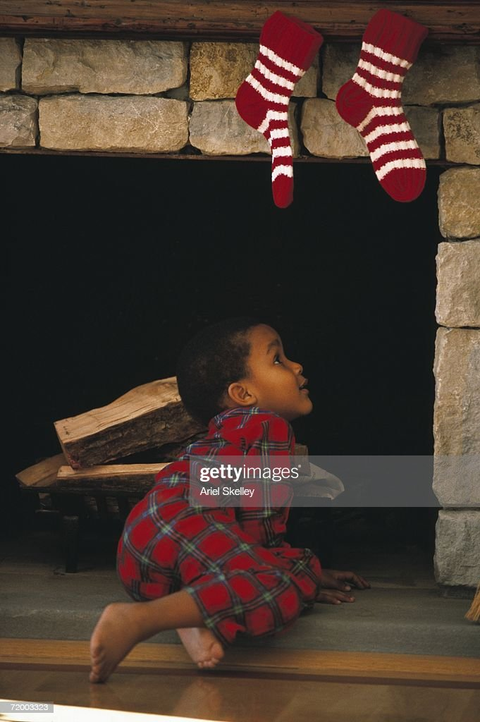 Young African boy looking up chimney with stockings hanging on it : Stock Photo