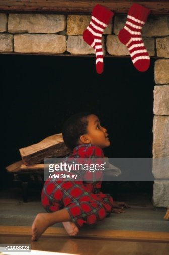 Young African boy looking up chimney with stockings hanging on it : Foto stock