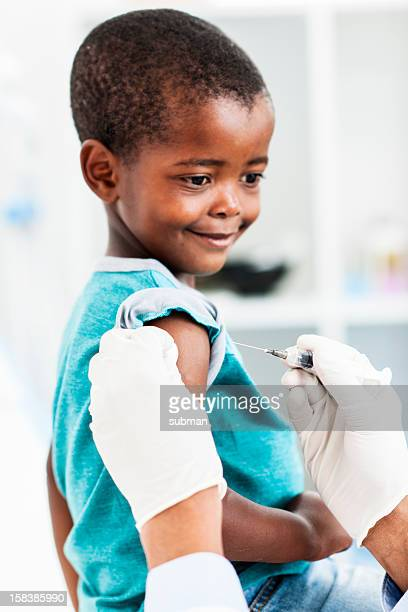 Young African boy smiling while getting a vaccination in arm